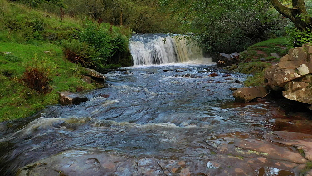 Aerial clip of river and waterfall in the Brecon Beacons National Park, Powys, Wales