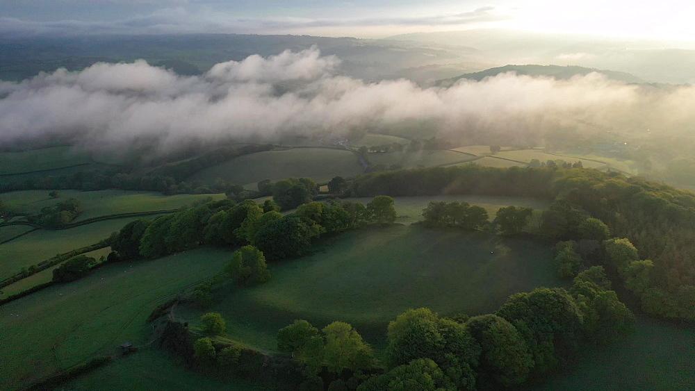 Aerial clip of Cadbury Castle Iron Age hillfort at dawn, Devon, England