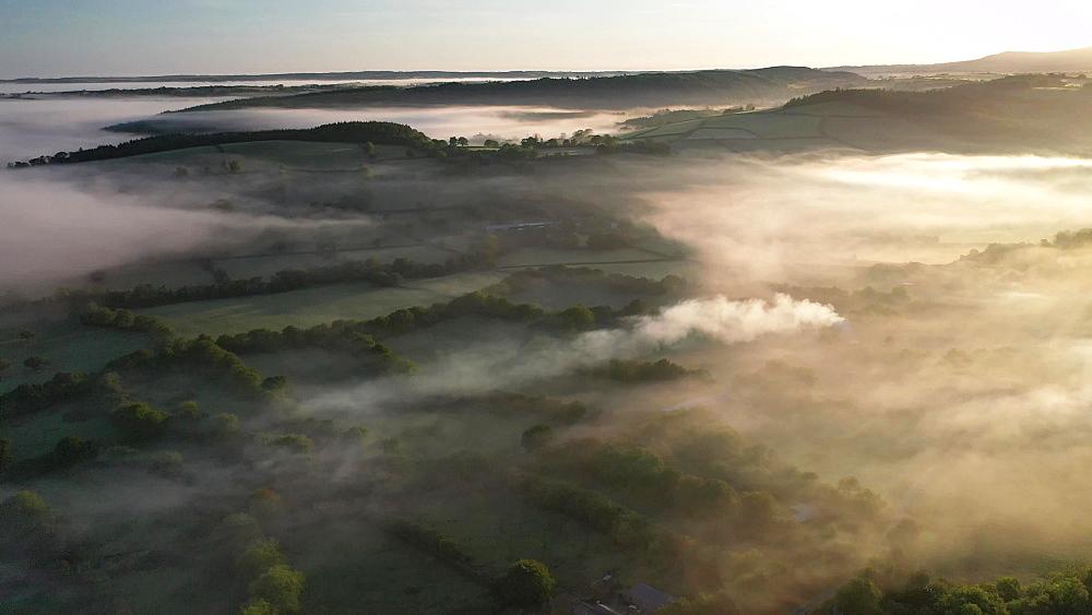 Aerial clip of rolling Devon countryside in dawn mist, Brentor, Devon, England