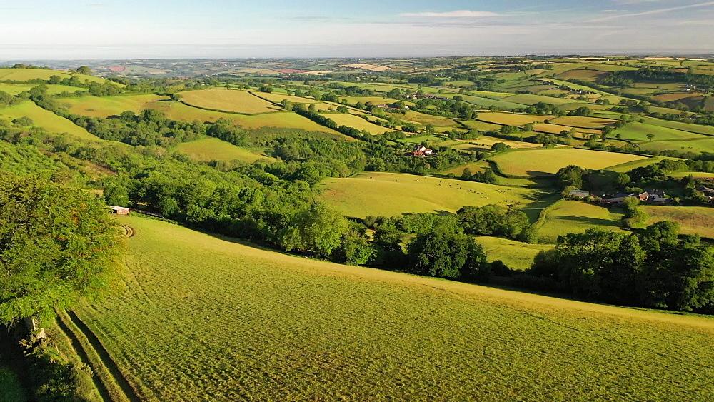 Aerial clip of rolling countryside near Cadbury Castle, Devon, England