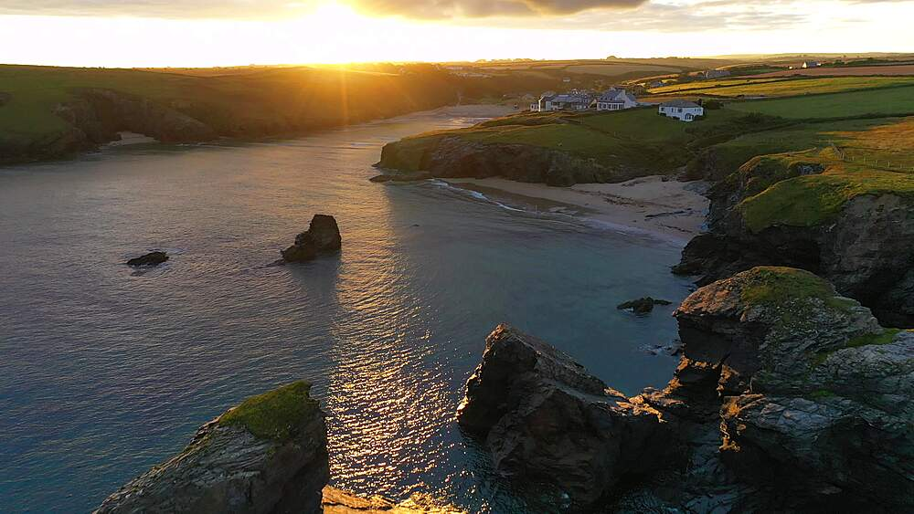 Aerial of sun rising over Porthcothan Beach and coastline, Cornwall, England, United Kingdom, Europe