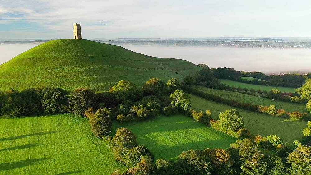 Aerial of Glastonbury Tor and surrounding countryside at dawn in late summer, Somerset, England, United Kingdom, Europe