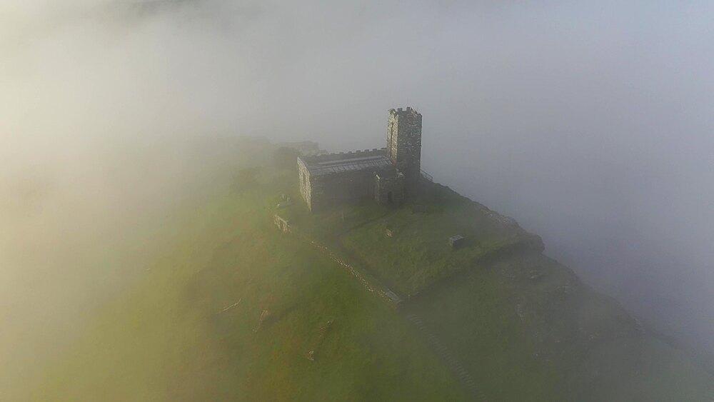 Aerial of Brentor Church surrounded by morning mist, Dartmoor, Devon, England, United Kingdom, Europe