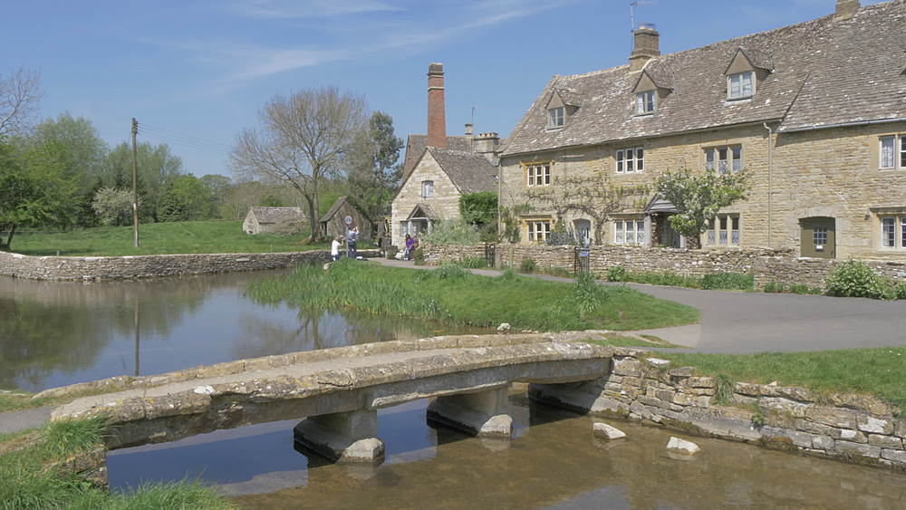 Footbridge over River Eye toward Old Mill Museum in Lower Slaughter, Cotswolds, Gloucestershire, England, United Kingdom, Europe