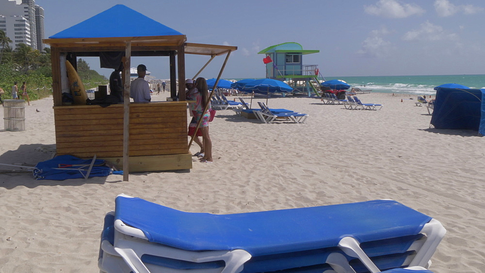 Roaming shot of beach hut and colourful lifeguard watchtower on Miami Beach, South Beach, Miami, Florida, United States of America, North America