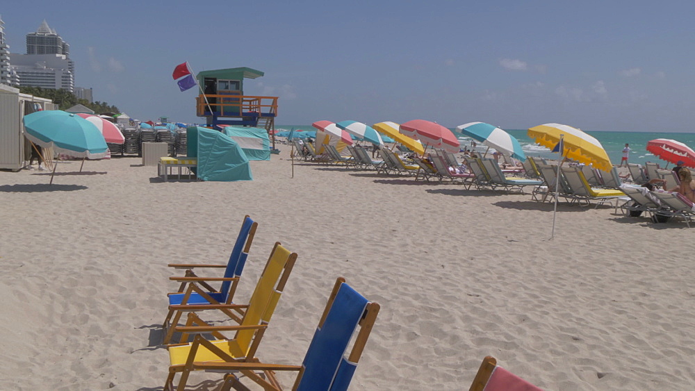 Lifting shot of colourful lifeguard watchtower and sunshades on Miami Beach, South Beach, Miami, Florida, United States of America, North America