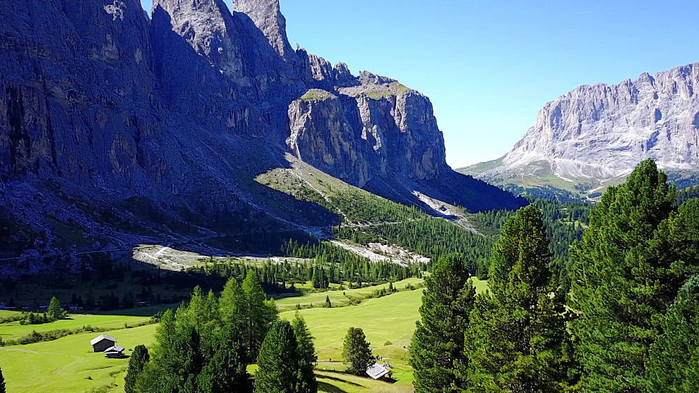 Flight through meadows and valley of Passo Gardena toward Selva Wolfenstein, Dolomites, South Tyrol, Italy, Europe