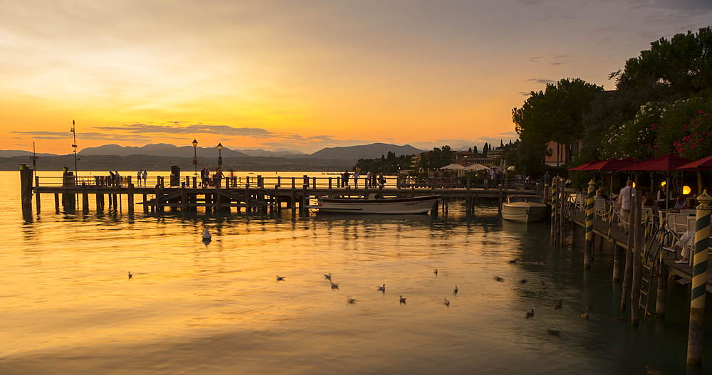 time lapse view of harbour activity after sunset, Sirmione, Lake Garda, Lombardy, Italy, Europe
