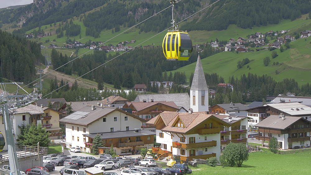 View cable cars passing village church in Corvara and surrounding mountain peaks, Alta Badia, Province of Belluno, Italian Dolomites, Italy, Europe