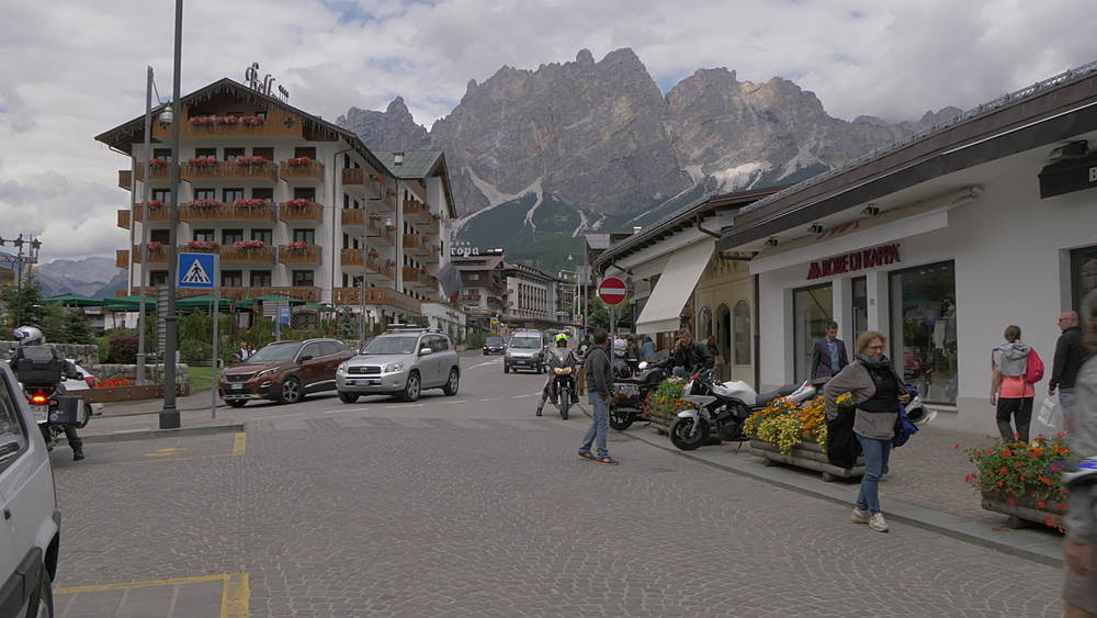 View of activity and mountains on main street in Cortina d'Ampezzo, Belluno, Dolomites, Italy, Europe