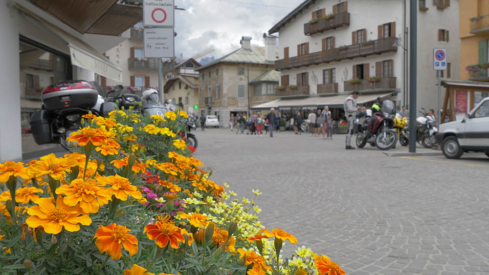 View of flowers and people on main street in Cortina d'Ampezzo, Belluno, Dolomites, Italy, Europe
