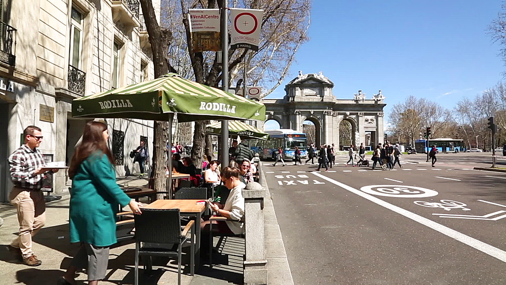 View of cafes and Independence Arch in Puerta de Alcala in bright sunshine, Madrid, Spain, Europe
