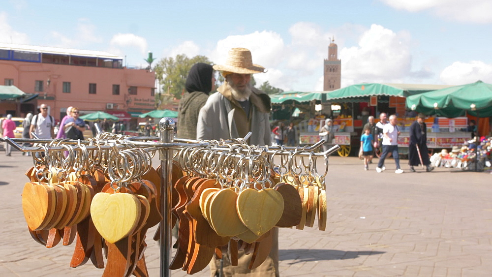 Tourists, taxis and activity on Djemaa el Fna showing Koutoubia Minaret, Marrakech, Morocco, North Africa, Africa
