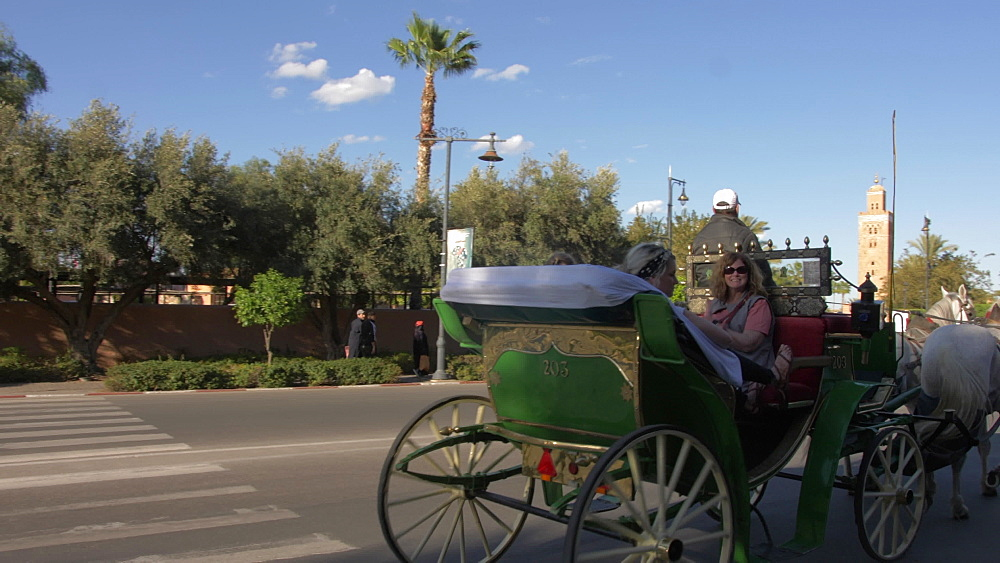 Roaming shot of horse and carriage and Koutoubia Minaret visible in background, Marrakech, Morocco, North Africa, Africa