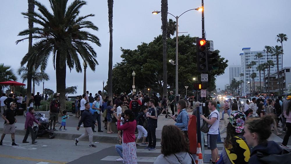 People around entrance to Santa Monica Pier at dusk, Santa Monica, Los Angeles, California, United States of America, North America