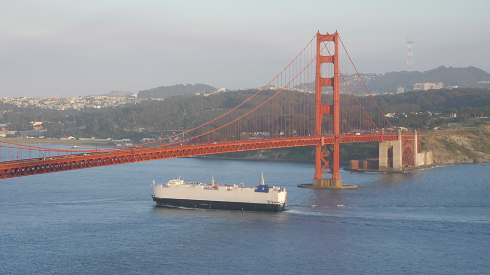 Freight ship sailing under the Golden Gate Bridge and city in background at sunset, San Francisco, California, United States of America, North America