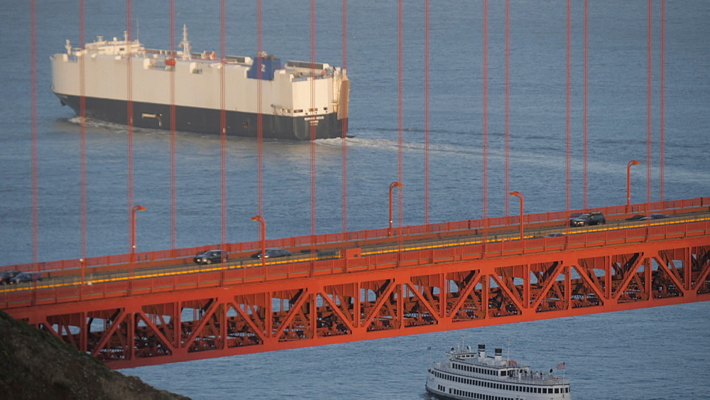 Freight ship sailing under the Golden Gate Bridge at sunset, San Francisco, California, United States of America, North America