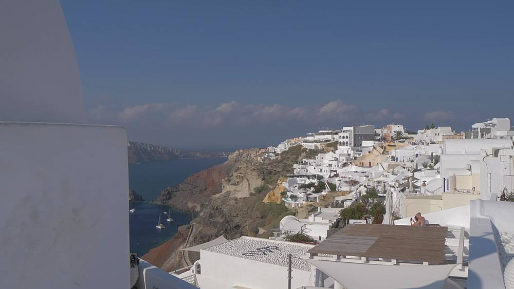 Roaming shot past little white chapel to view of Med Sea and village of Oia, Santorini, Cyclades, Greek Islands, Greece, Europe