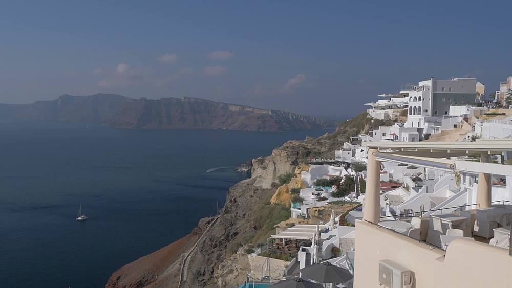 Crane shot of white washed houses and Med Sea in Oia, Santorini, Cyclades, Greek Islands, Greece, Europe