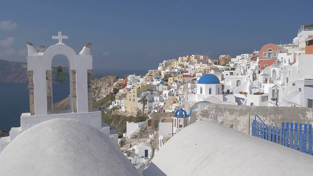 Slider shot of white washed houses and blue domed chapels in Oia, Santorini, Cyclades, Greek Islands, Greece, Europe