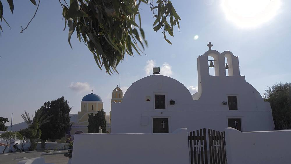 Slider shot of little white chapel and Saint George Church in Oia, Santorini, Cyclades, Greek Islands, Greece, Europe