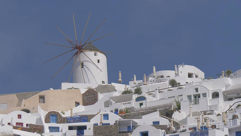 Panning shot of clifftop village of Oia from small harbour, Santorini, Cyclades, Greek Islands, Greece, Europe