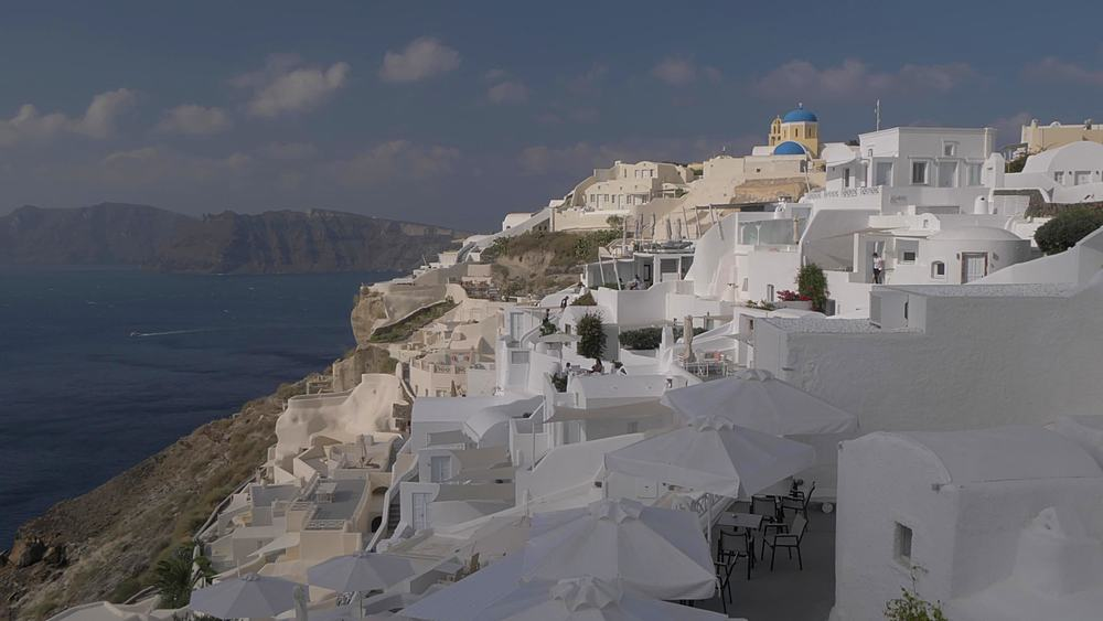 Panning shot of Mediterranean Sea and Oia during morning, Santorini, Cyclades, Greek Islands, Greece, Europe