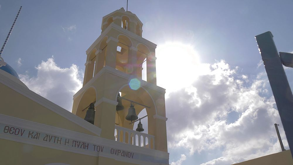 Slider shot of Saint George Church Belltower in Oia against sun, Santorini, Cyclades, Greek Islands, Greece, Europe