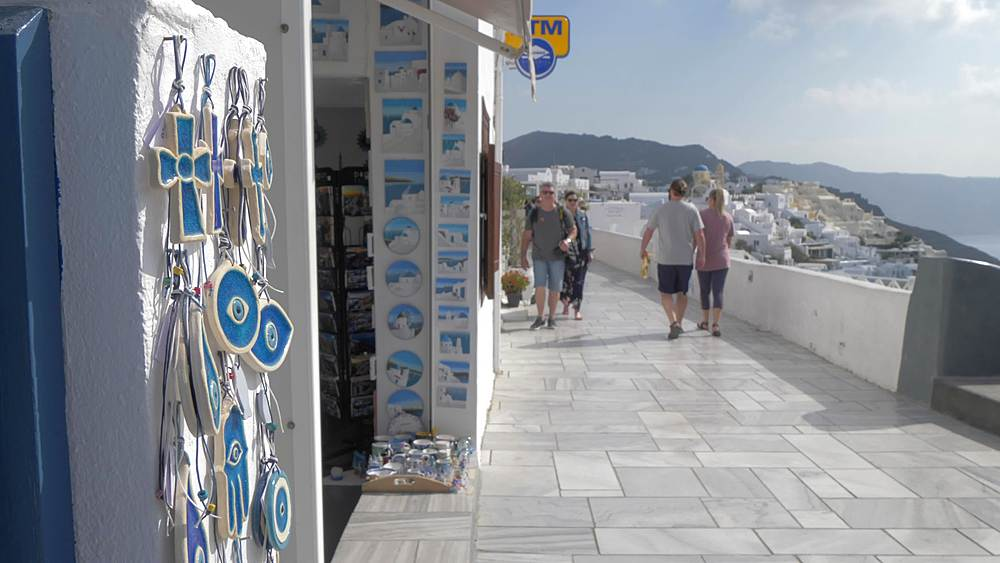 Still shot of visitors on street overlooking white washed village of Oia, Santorini, Cyclades, Greek Islands, Greece, Europe