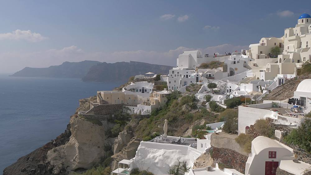 Panning shot of white washed village of Oia, Santorini, Cyclades, Greek Islands, Greece, Europe