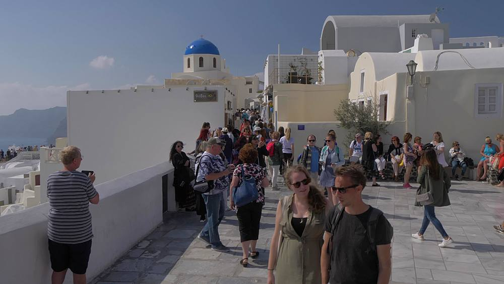 Roaming shot of street and visitors of white washed village of Oia, Santorini, Cyclades, Greek Islands, Greece, Europe