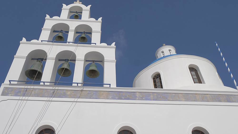 Roaming shot of Ekklisia Panagia Platsani in white washed village of Oia, Santorini, Cyclades, Greek Islands, Greece, Europe