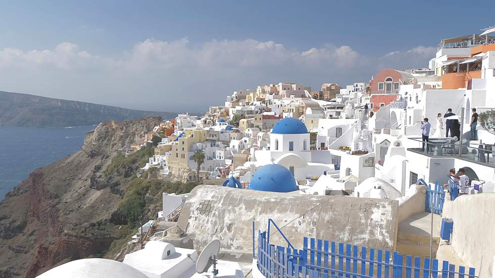 Roaming shot of belltowers and blue and white domes in village of Oia, Santorini, Cyclades, Greek Islands, Greece, Europe