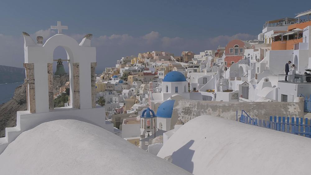 Panning shot of belltowers and blue and white domes in village of Oia, Santorini, Cyclades, Greek Islands, Greece, Europe