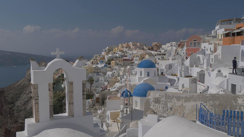 Crane shot of belltowers and blue and white domes in village of Oia, Santorini, Cyclades, Greek Islands, Greece, Europe