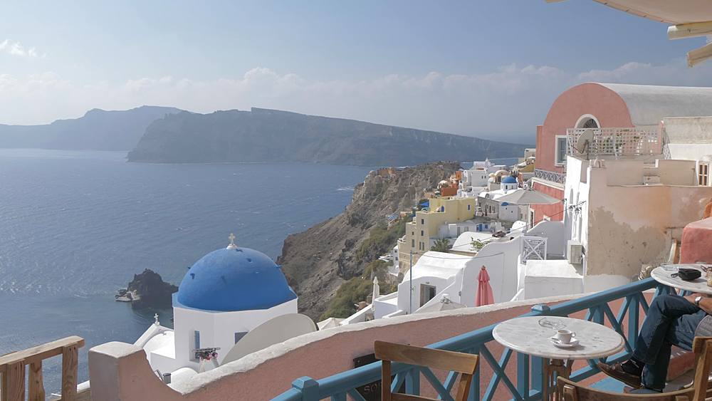 Panning shot of cafe and blue and white domes in village of Oia, Santorini, Cyclades, Greek Islands, Greece, Europe