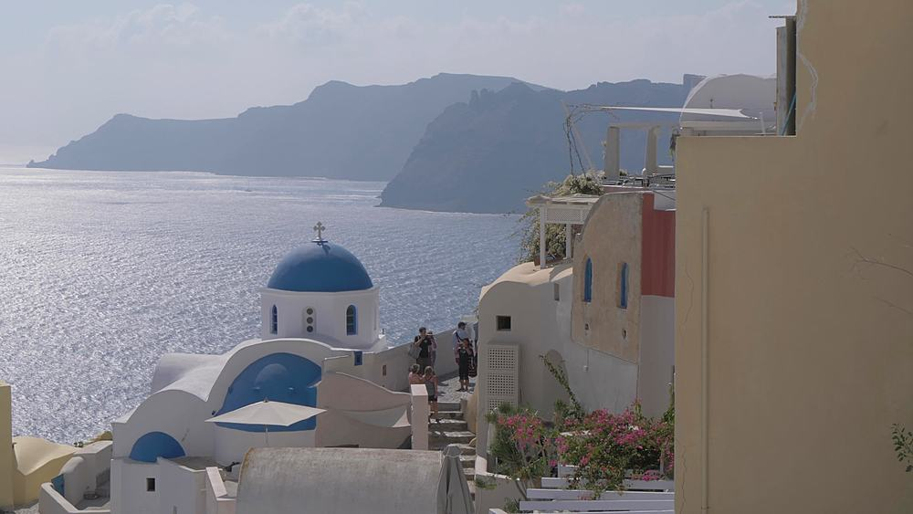 Tilting shot of blue and white dome church in village of Oia, Santorini, Cyclades, Greek Islands, Greece, Europe