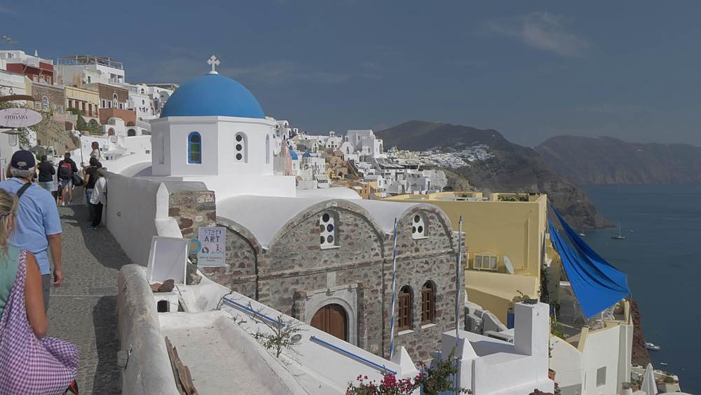 Panning shot of blue and white dome church to the Med in village of Oia, Santorini, Cyclades, Greek Islands, Greece, Europe