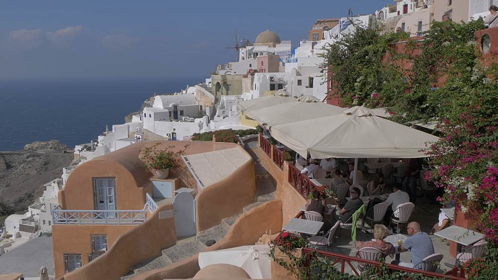 Panning shot from above to windmill and restaurant in village of Oia, Santorini, Cyclades, Greek Islands, Greece, Europe