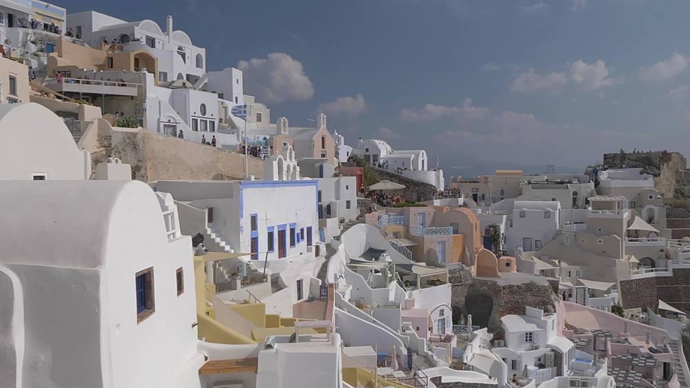 Panning shot from the Med to white washed houses in village of Oia, Santorini, Cyclades, Greek Islands, Greece, Europe