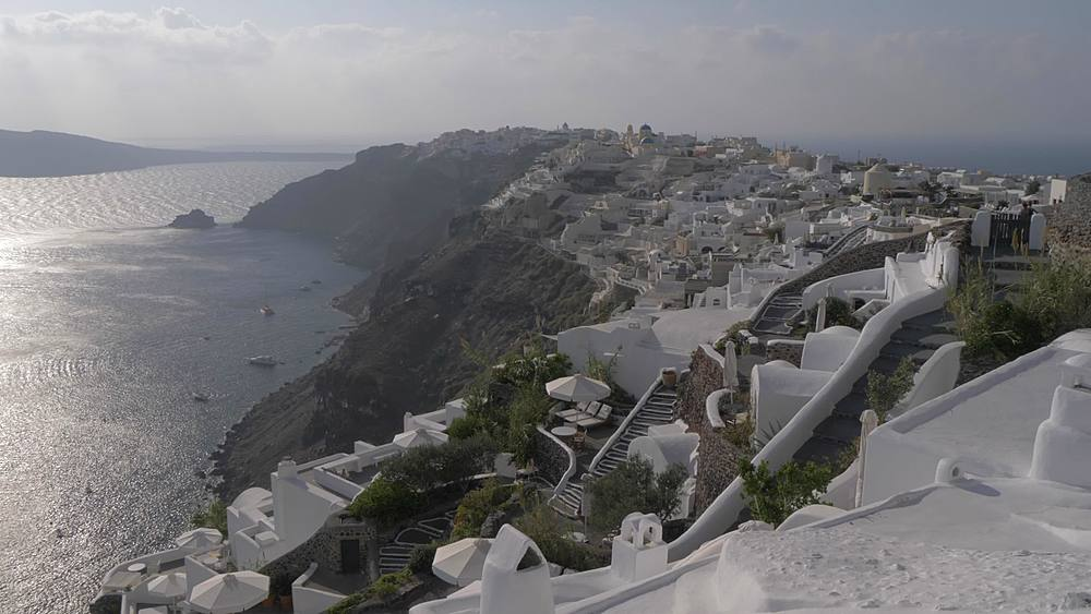 Panning shot from the Med to white washed village of Oia at sunset, Santorini, Cyclades, Greek Islands, Greece, Europe