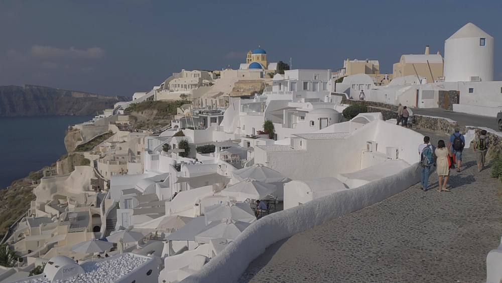Panning shot from the Med to white washed village of Oia in morning, Santorini, Cyclades, Greek Islands, Greece, Europe