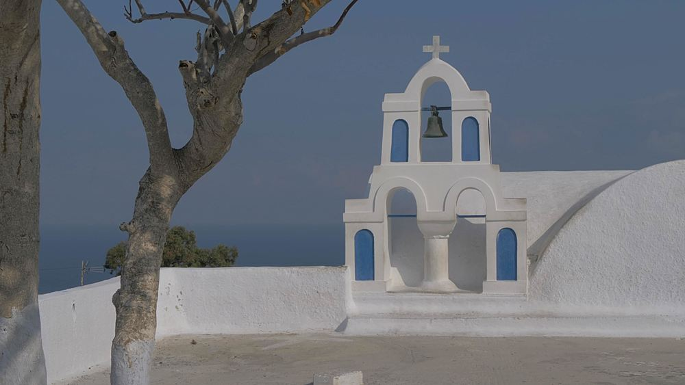 Panning shot of little white washed wedding chapel in village of Oia, Santorini, Cyclades, Greek Islands, Greece, Europe