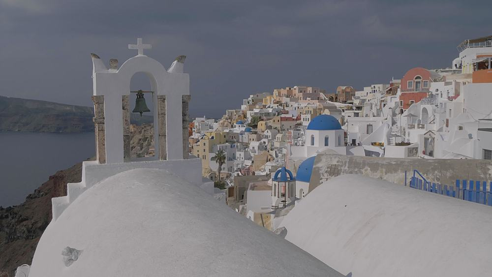 Panning shot of white washed bell tower in village of Oia, Santorini, Cyclades, Greek Islands, Greece, Europe