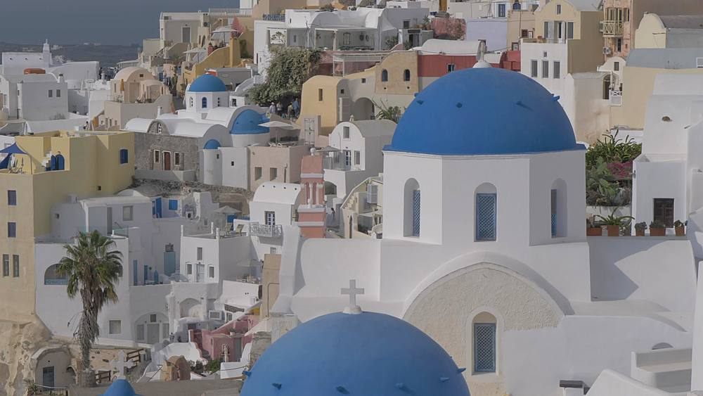 Tilting shot of blue domed chapel and white washed bell tower in village of Oia, Santorini, Cyclades, Greek Islands, Greece, Europe