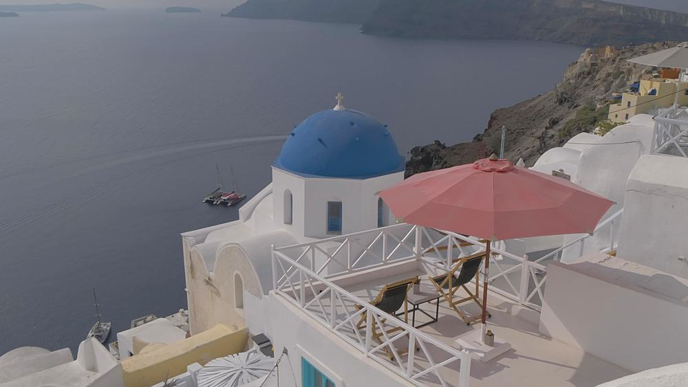 Panning shot of blue domed chapel and white washed houses on clifftop in village of Oia, Santorini, Cyclades, Greek Islands, Greece, Europe