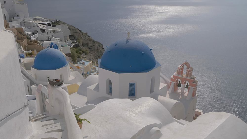 Panning shot of blue domed chapels and white washed houses on clifftop in village of Oia, Santorini, Cyclades, Greek Islands, Greece, Europe