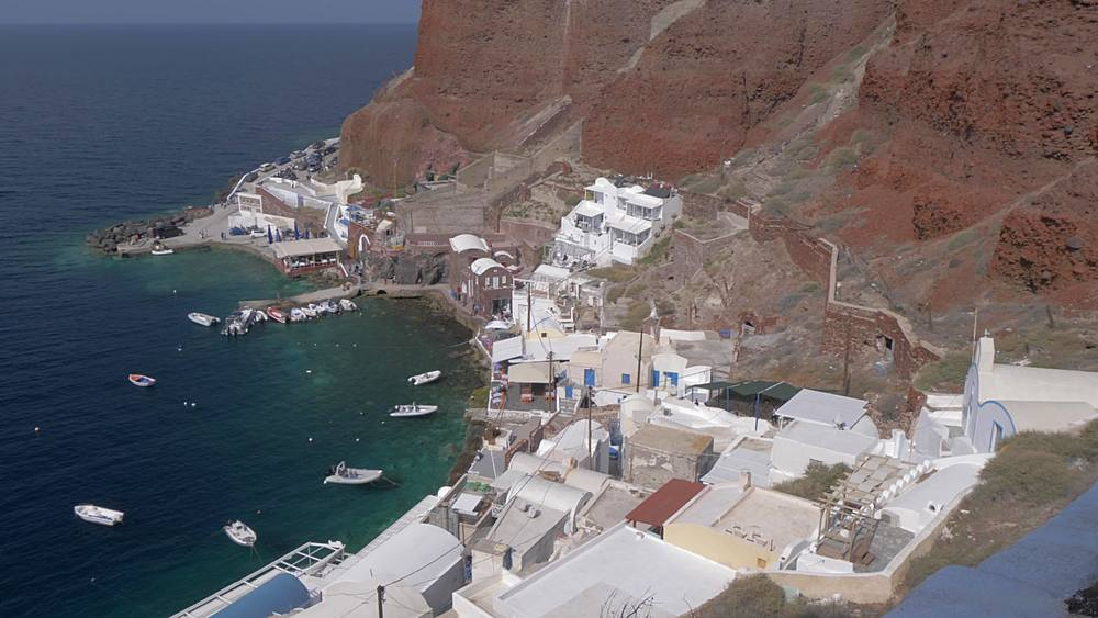 Elevated view of red cliffs and small harbour in village of Oia, Santorini, Cyclades, Greek Islands, Greece, Europe