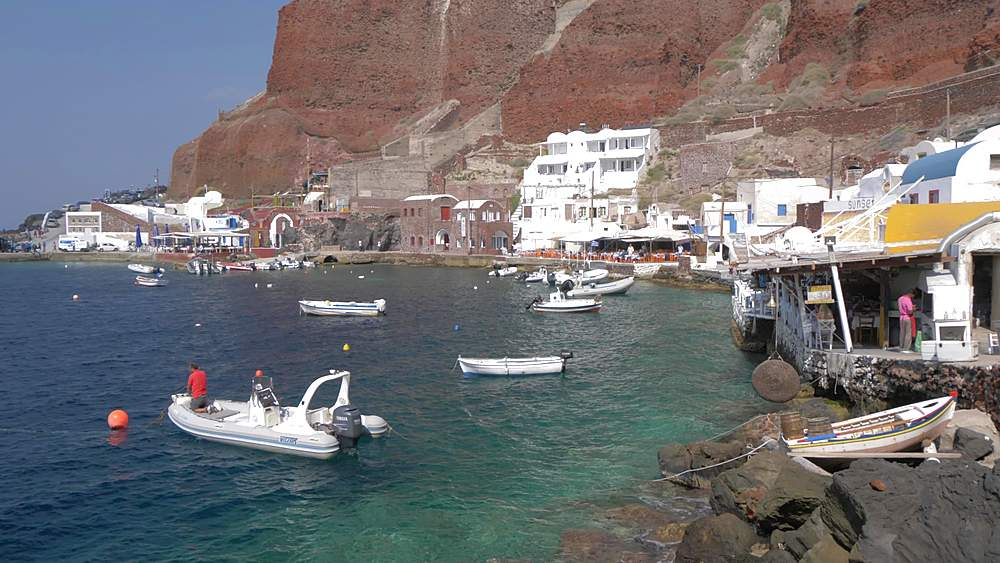 View of clifftop town and small harbour in village of Oia, Santorini, Cyclades, Greek Islands, Greece, Europe