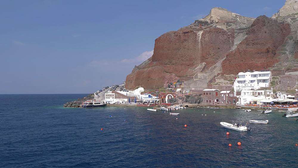 Panning shot of small harbour in village of Oia, Santorini, Cyclades, Greek Islands, Greece, Europe